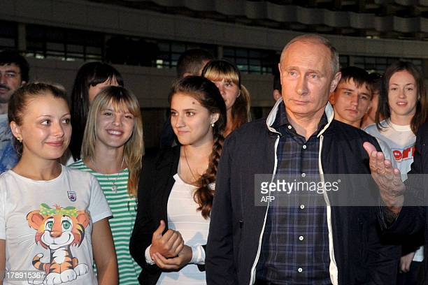 Russia's President Vladimir Putin stands next to children evacuated from the flooded areas of the Russia's Far Eastern Khabarovsk region during their...