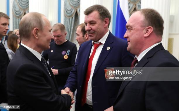 Russia's President Vladimir Putin talks to Russian national ice hockey team head coach Oleg Znarok at a reception after a ceremony to present state...