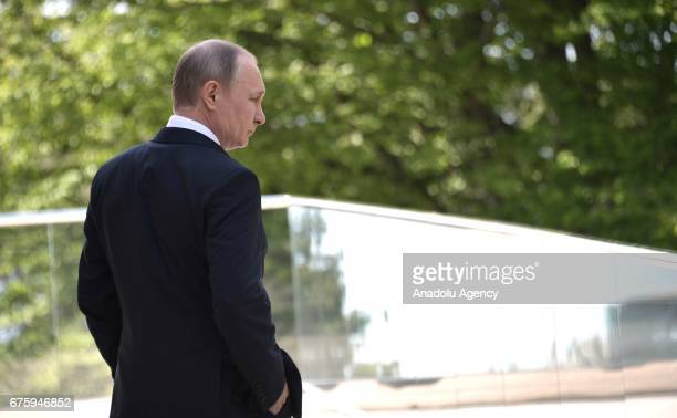 Russia's President Vladimir Putin waits for the arrival of German Chancellor Angela Merkel at Bocharov Ruchei residence in Sochi Russia on May 2 2017