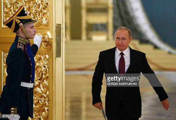 Russia's President Vladimir Putin walks past an honour guard as he attends a session of the Council for Civil Society and Human Rights at the Kremlin...