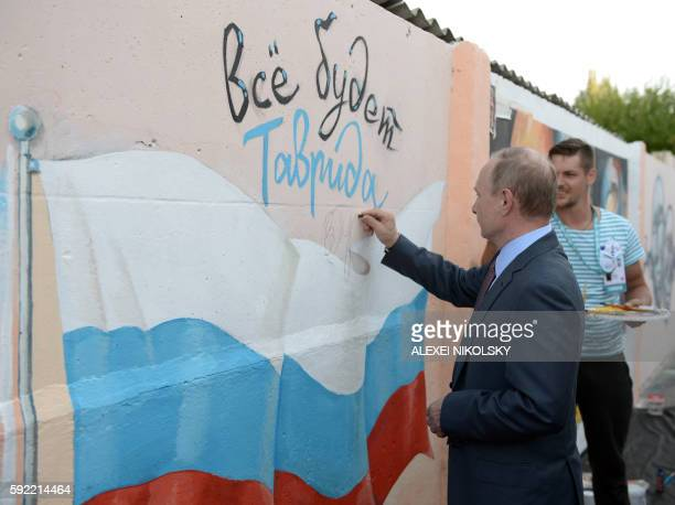 Russia's President Vladimir Putin writes his signature on a graffiti in the youth educational forum 'Tavrida' in Crimea on August 19 2016