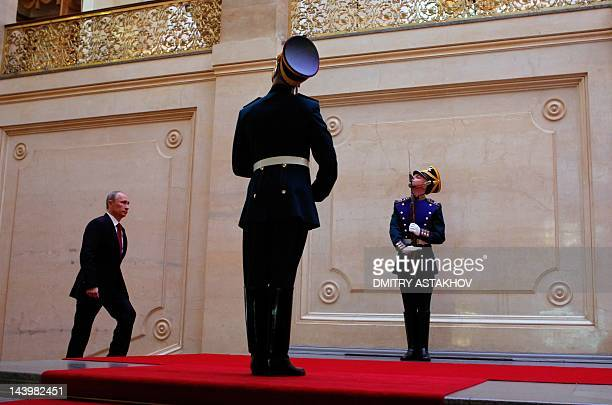 Russia's president-elect Vladimir Putin walks past Presidential regiment's honour guards in the Great Kremlin Palace in Moscow's Kremlin, on May 7 as...
