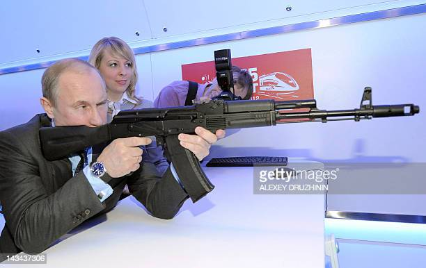 Russia's Prime Minister and Presidentelect Vladimir Putin aims at a target with a replica of Kalashnikov assault rifle in Moscow on April 26 while...