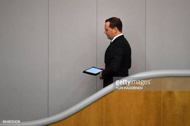 TOPSHOT Russia's Prime Minister Dmitry Medvedev walks downstairs in the lower house of Russian parliament the State Duma prior his speech in State...