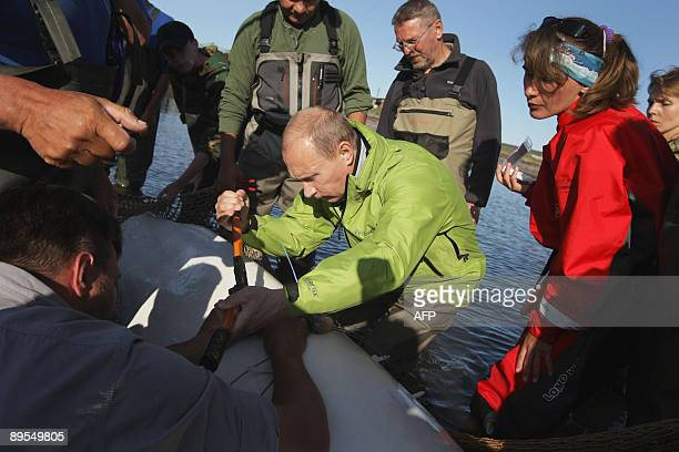 Russia's Prime Minister Vladimir Putin attaches a satellite tracking tag to a Beluga whale named Dasha as he visits Chkalov island, 700 kilometres...