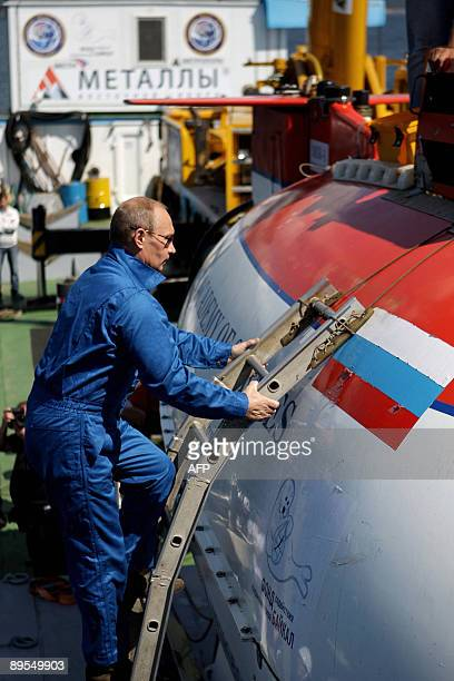 Russia's Prime Minister Vladimir Putin climbs onboard of the Mir2 minisubmersible on which he intends to dive into the depths of Lake Baikal on...