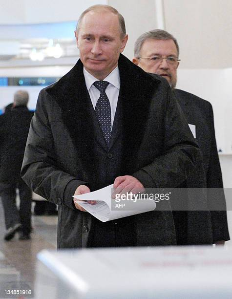 Russia's Prime Minister Vladimir Putin holds his ballot he votes for parliamentary election at a polling station in Moscow on December 4 2011...