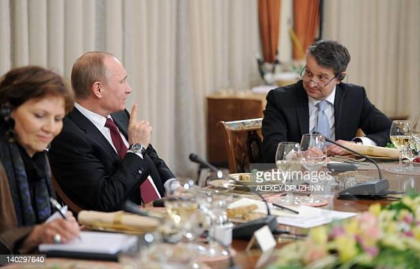 Russia's Prime Minister Vladimir Putin listens to Handelsblatt chief editor Gabor Steingart as Le Monde chief editor Sylvie Kauffmann writes down...