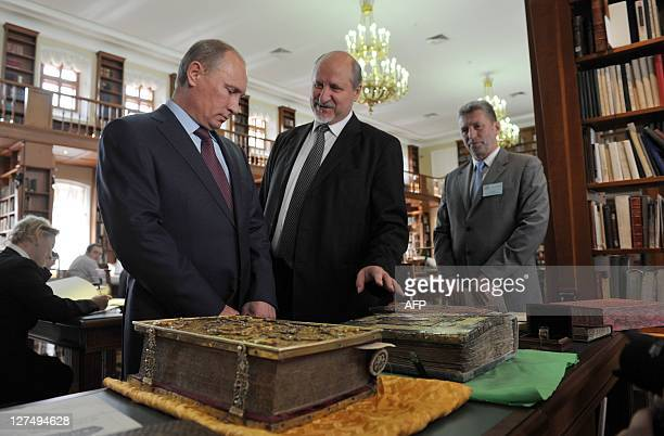 Russia's Prime Minister Vladimir Putin looks at ancient books during his visit to the Russian State Library in Moscow on September 28 2011 AFP PHOTO/...