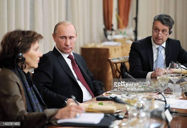 Russia's Prime Minister Vladimir Putin looks at Le Monde chief editor Sylvie Kauffmann as Handelsblatt chief editor Gabor Steingart speaks during...