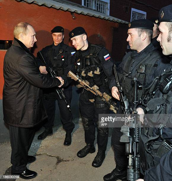 Russia's Prime Minister Vladimir Putin shakes hands with local Federal Security Service special forces officers during a visit to the Chechnya's...