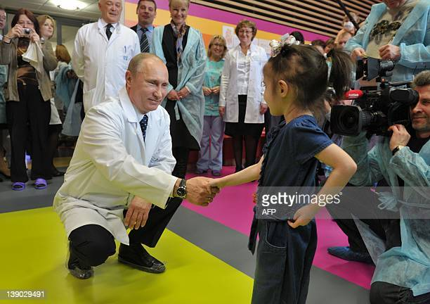 Russia's Prime Minister Vladimir Putin socializes with a young patient as he visits the Federal Scientific Clinical Center of Pediatric Hematology...