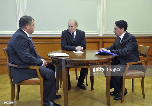Russia's Prime Minister Vladimir Putin speaks with Defence Minister Anatoly Serdyukov and the head of Uralvagonzavod company Oleg Sienko during their...