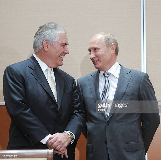 Russia's Prime Minister Vladimir Putin speaks with ExxonMobil President and Chief Executive Officer Rex Tillerson during the signing of a...