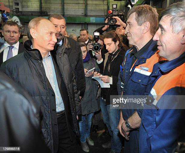 Russia's Prime Minister Vladimir Putin speaks with workers during his visit to the Proletarsky machine building plant in StPetersburg on October 20...