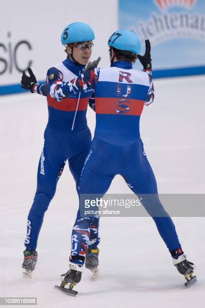 Russia's Semen Elistratov and Dmitry Migunov react after crossing the finish line during the men's 5000 m relay final at the ISU Short track World...