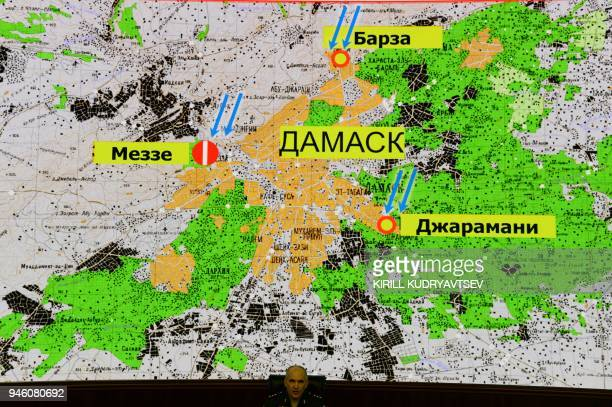 Russia's senior military officer Sergei Rudskoi sits before a map of Damascus showing alleged strikes locations during a briefing at the Russian...
