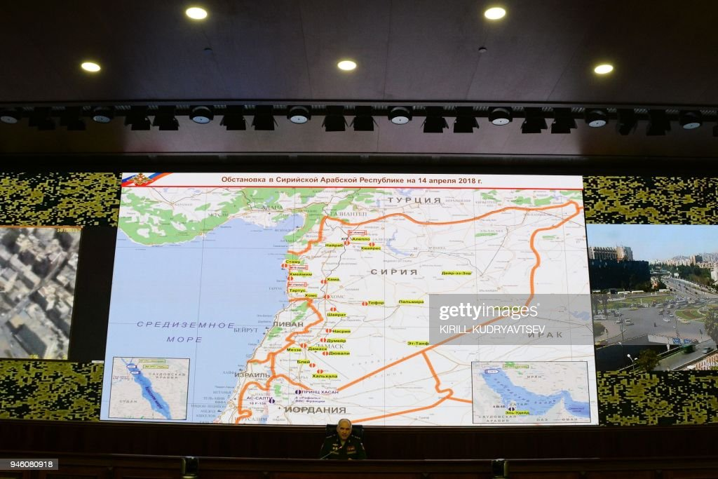 Russia's senior military officer Sergei Rudskoi sits bellow a map of Syria screened during a briefing at the Russian Defence Ministry headquarters in Moscow on April 14, 2018. The Russian military said on April 14, 2018 that Western allies fired 103 cruise missiles including Tomahawk missiles at Syria but that Syrian air defence systems managed to intercept 71 of them. The US, Britain and France conducted joint strikes overnight on April 14 against the Syrian regime of Bashar al-Assad in response to alleged chemical weapons attacks. / AFP PHOTO / Kirill KUDRYAVTSEV