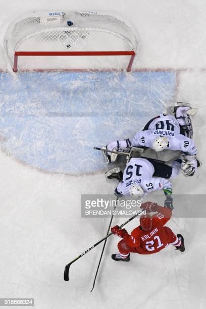 Russia's Sergei Kalinin reacts as teammate Russia's Ilya Kovalchuk scores against Slovenia's Luka Gracnar and Blaz Gregorc in the men's preliminary...