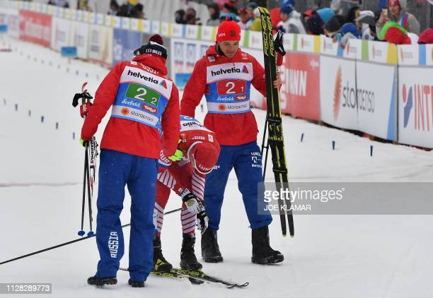 Russia's Sergey Ustiugov reacts flanked by Russia's Alexander Bessmertnykh and Russia's Andrey Larkov after the Men's cross country skiing relay...