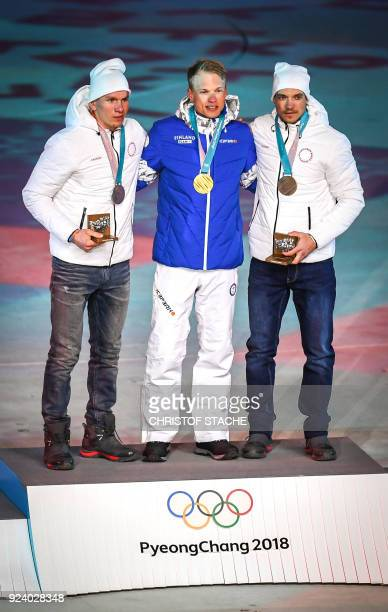Russia's silver medallist Alexander Bolshunov Finland's gold medallist Iivo Niskanen and Russia's bronze medallist Andrey Larkov pose on the podium...