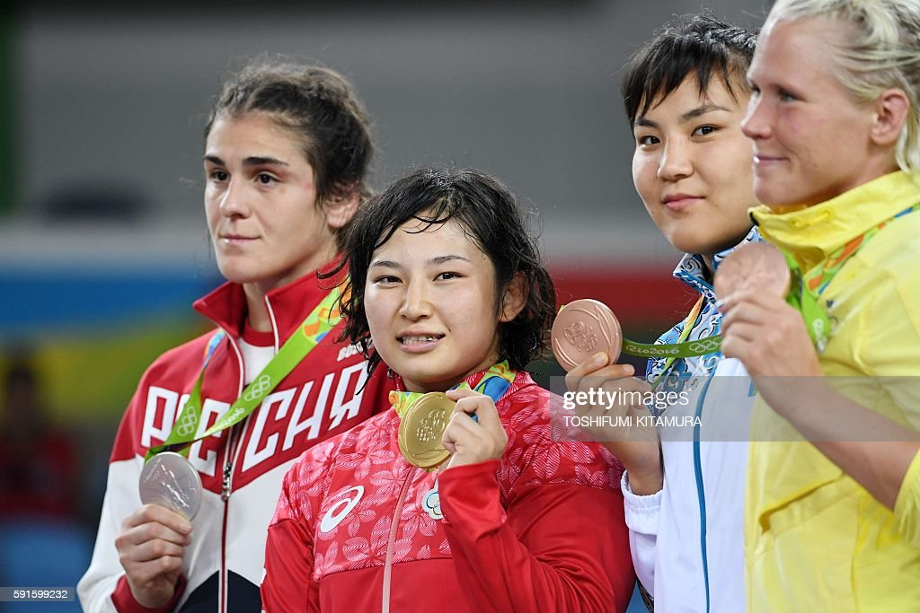 Russia's silver medallist Natalia Vorobeva, Japan's gold medallist Sara Dosho, Kazakhstan's bronze medallist Elmira Syzdykova and Sweden's Anna Jenny Fransson celebrate on the podium at the end of the women's 69kg freestyle wrestling event at the Carioca Arena 2 in Rio de Janeiro on August 17, 2016, during the Rio 2016 Olympic Games. / AFP / Toshifumi KITAMURA