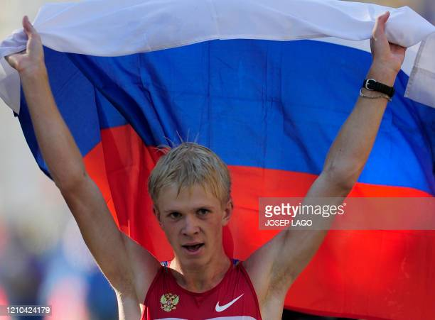 Russia's Stanislav Emelyanov celebrates with a russian flag after winning the men's 20km walk at the 2010 European Athletics Championships at the...