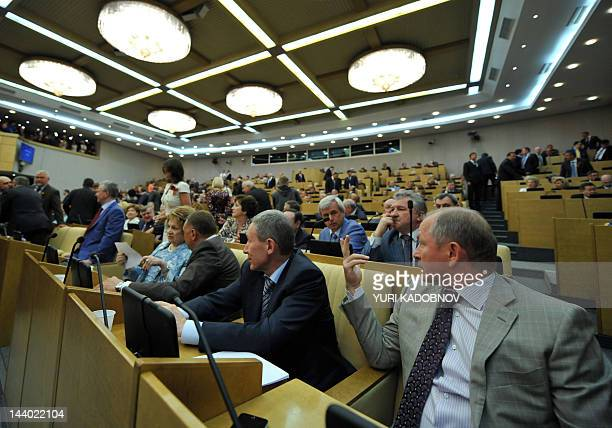 Russia's State Duma deputies speak before their meeting with Russian President Vladimir Putin and former President Dmitry Medvedev in Moscow on May 8...