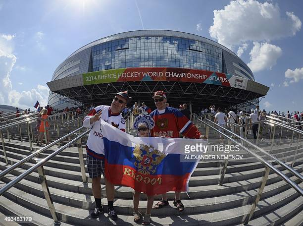 Russia's team fans pose for a photo with a banner bearing the colours of Russian national flag and Russian coat of arms the twoheaded eagle in front...