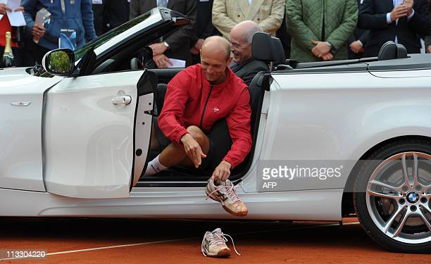 Russia's tennis player Nikolay Davydenko takes off his shoes as he sits in his new car which was his prize for winning the ATP tennis BMW Open final...
