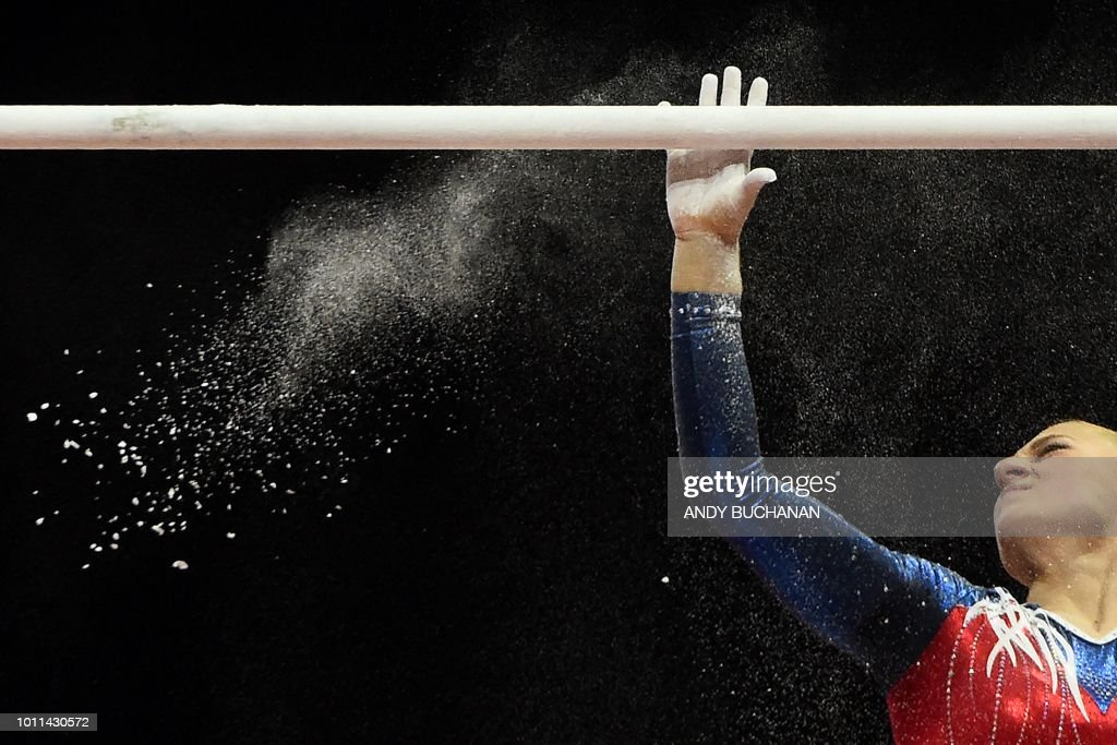 TOPSHOT - Russia's Uliana Perebinosova powders the bar before competing in the women's uneven bars final of the artistic gymnastics at the SSE Hydro during the 2018 European Championships in Glasgow on August 5, 2018.