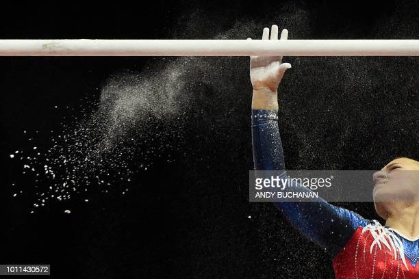 TOPSHOT Russia's Uliana Perebinosova powders the bar before competing in the women's uneven bars final of the artistic gymnastics at the SSE Hydro...