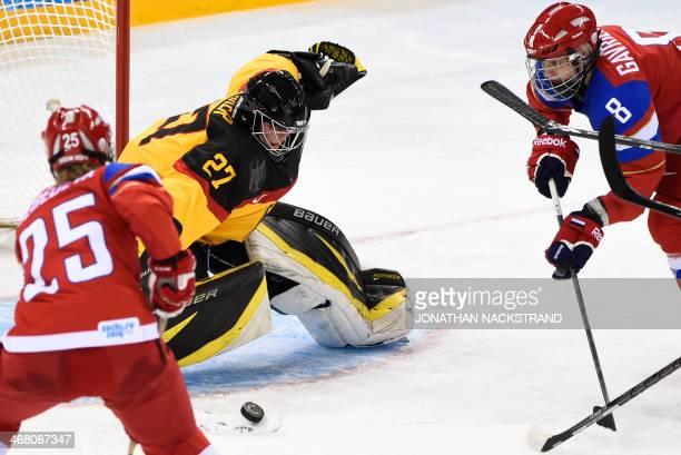 Russia's Yekaterina Lebedeva and Iya Gavrilova try to score against Germany's goalkeeper Viona Harrer during a Women's Ice Hockey Group B match...