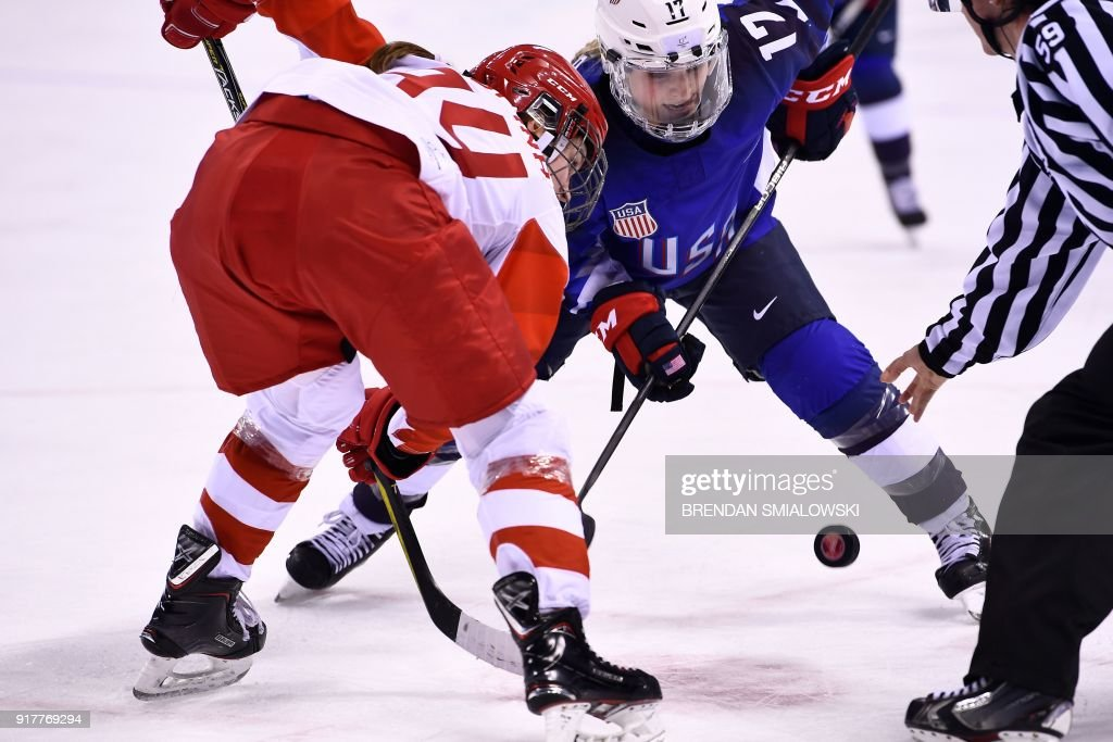 TOPSHOT - Russia's Yevgenia Dyupina (L) and USA's Jocelyne Lamoureux-Davidson face off in the women's preliminary round ice hockey match between the US and Olympic Athletes from Russia during the Pyeongchang 2018 Winter Olympic Games at the Kwandong Hockey Centre in Gangneung on February 13, 2018. / AFP PHOTO / Brendan Smialowski