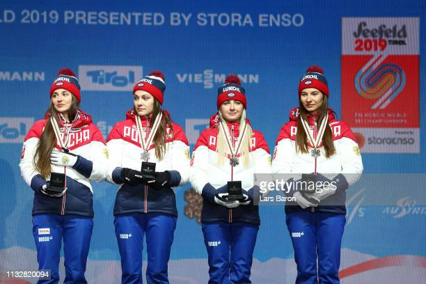 Russias Yulia Belorukova Anastasia Sedova Anna Nechaevskaya and Natalia Nepryaeva celebrate their bronze medal following the Women's 4x5km Cross...