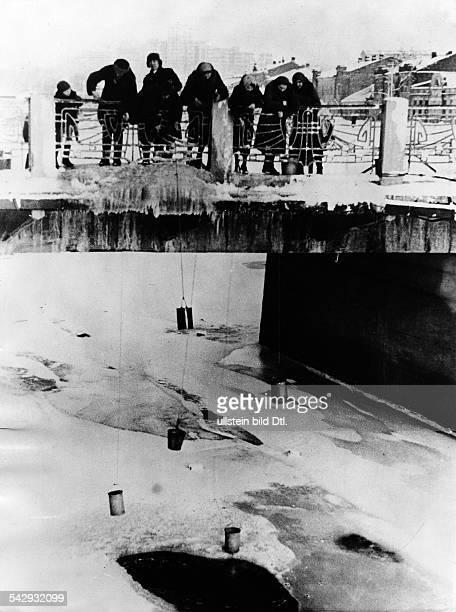 russische Zivilbevölkerung in Charkow auf einer Brücke um Wasser zu schöpfen 1942
