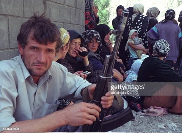 Russland Tschetschenien Grosny TschetschenienKonflikt tschetschenischer Mann mit Gewehr im Hintergrund Frauen August 2003