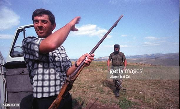 Russland, Tschetschenien - Tschetschenien-Konflikt - tschetschenischer Mann mit einem Gewehr, im Hintergrund Soldat einer tschetschenischen...