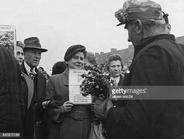 Russlandheimkeher im Lager Friedland Frauen mit Fotos ihrer vermissten Angehörigen hoffen von den Heimkehrern Auskunft zu erhalten 1955