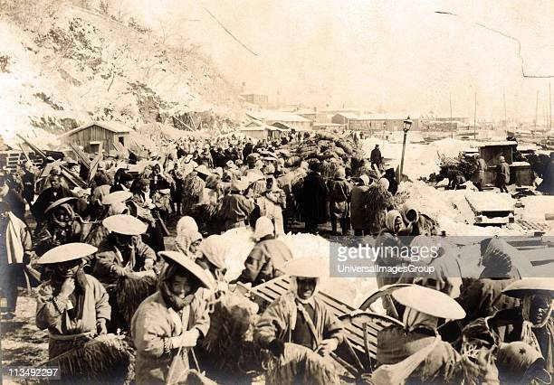 Japanese and Korean coolies removing supplies from the wharf at Chemulpo Korea 1904