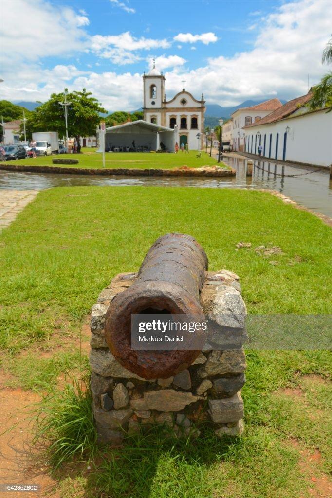 Rusted ancient defensive cannon and Capela de Santa Rita in Paraty, Rio de Janeiro : Stock Photo