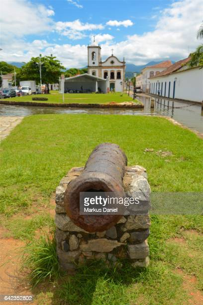Rusted ancient defensive cannon and Capela de Santa Rita in Paraty, Rio de Janeiro