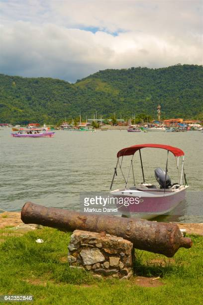 Rusted ancient defensive cannon and day trip tourist boats in Paraty, Rio de Janeiro