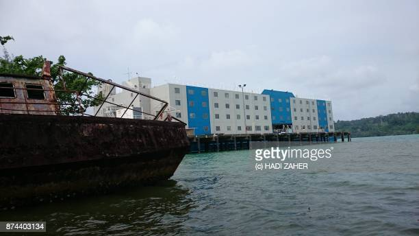 A rusted broken boat and an accommodation ship