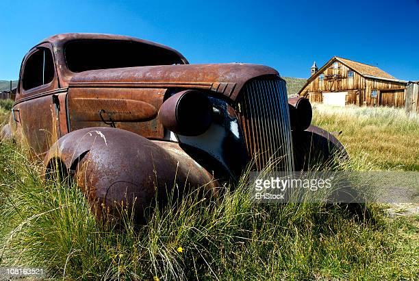 Oxidadas de automóviles en campo con Barn ciudad fantasma de Bodie California