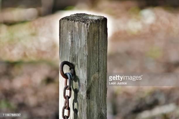 rusted chain hanging on wooden post - coluna de madeira - fotografias e filmes do acervo