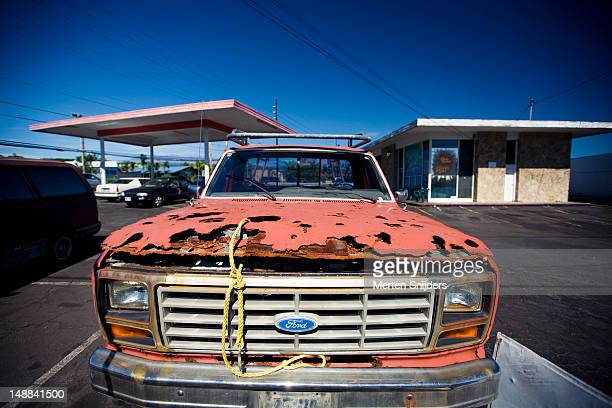 Rusted old Ford at gas station on Kino'ole street.
