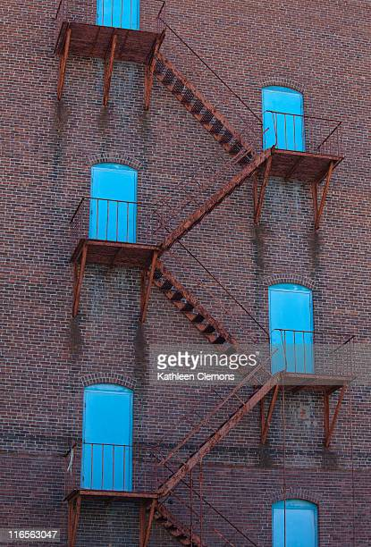 Rusted staircase leads to 6 bright blue doors