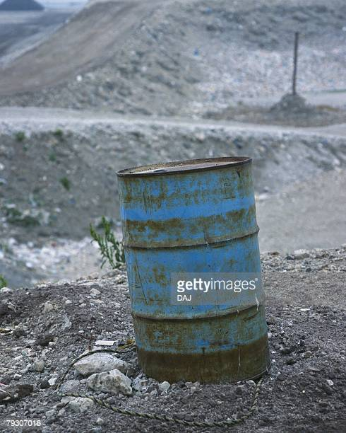 Rusted waste drum in landfill, high angle view