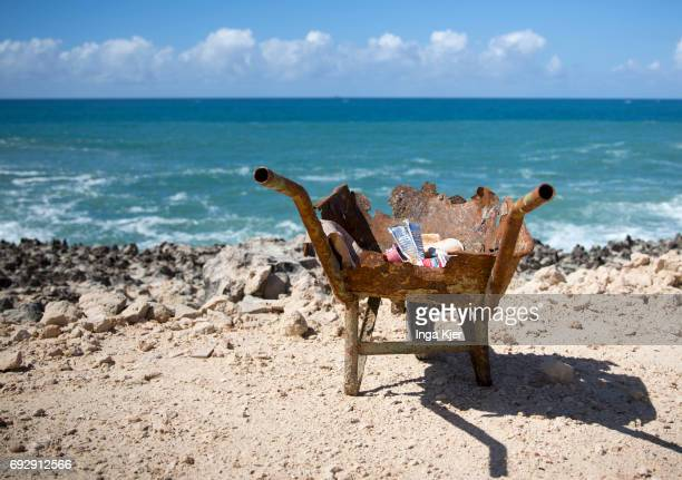 A rusted wheelbarrow filled with garbage stands on the beach of Mogadishu on May 01 2017 in Mogadischu Somalia